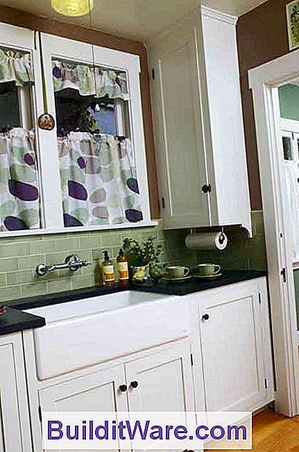 Die Küche Verfügt über Stilvolle Weiße Schränke, Einbauten Und Originale  Leuchten.